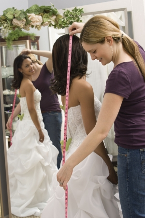 Caucasian seamstress measuring African-American bride in bridal shop. photo