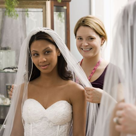 africanamerican: Caucasian seamstress helping African-American bride with veil in bridal shop. Stock Photo