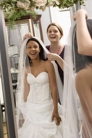 saleswomen: Caucasian seamstress helping African-American bride with veil in bridal shop. Stock Photo
