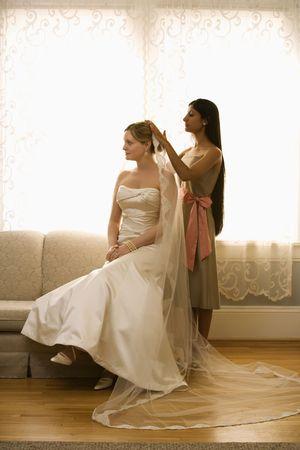 Indian bridesmaid placing veil on Caucasian bride. photo