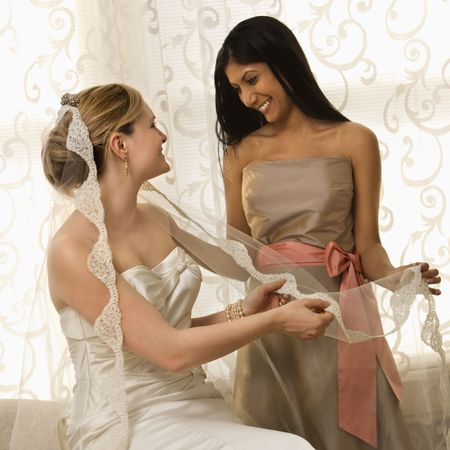 Indian maid of honor holding Caucasian bride's veil. Stock Photo - 2145454