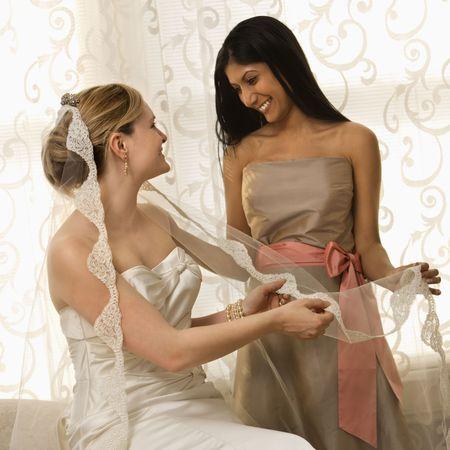bridesmaid: Indian maid of honor holding Caucasian brides veil.