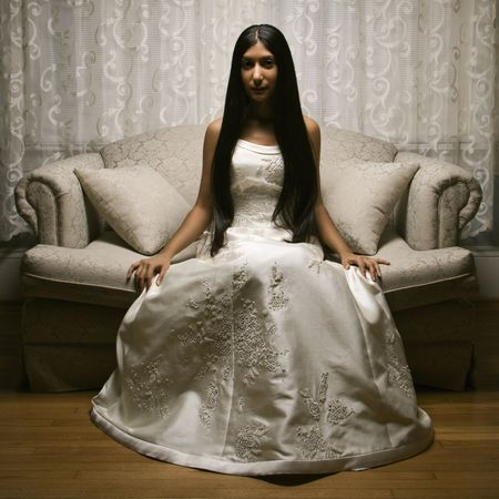 Portrait of an Indian bride sitting on a love seat. Stock Photo - 2145180