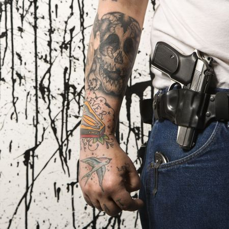 nonconformity: Caucasian tattooed man wearing holster with gun.