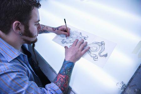 Caucasian male tattoo artist drawing tattoo on light table.