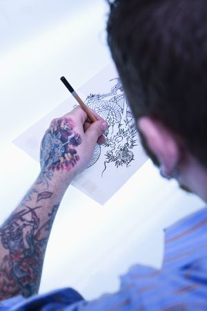 dragon vertical: Caucasian male tattoo artist drawing tattoo on light table.