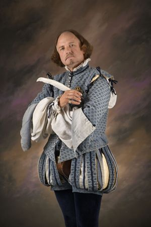 bard: William Shakespeare in period clothing holding feather pen and looking at viewer. Stock Photo