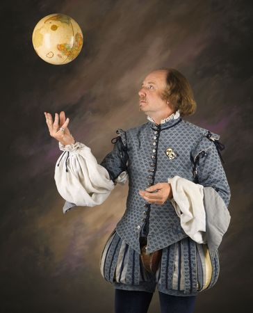bard: William Shakespeare in period clothing tossing globe into air. Stock Photo