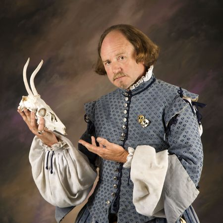 William Shakespeare in period clothing holding deer skull and looking at viewer.