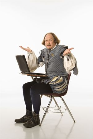 facial expression: William Shakespeare in period clothing sitting in school desk with laptop and shrugging at viewer.