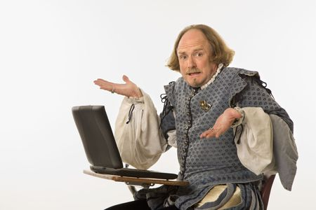 William Shakespeare in period clothing sitting in school desk with laptop computer shrugging at viewer. Stock Photo