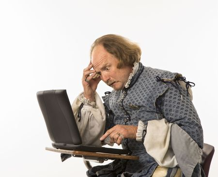 computer language: William Shakespeare in period clothing sitting in school desk with laptop computer and hand to head looking perplexed. Stock Photo
