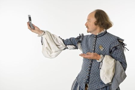 William Shakespeare in period clothing holding cell phone and gesturing. photo