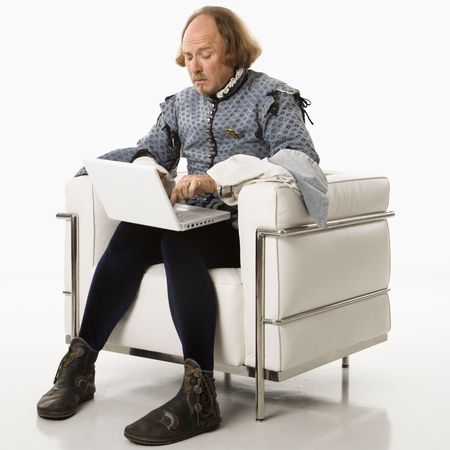 william shakespeare: William Shakespeare in period clothing sitting on modern chair using laptop.