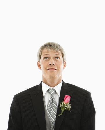 boutonniere: Portrait of Caucasian male in tuxedo with boutonniere looking up.