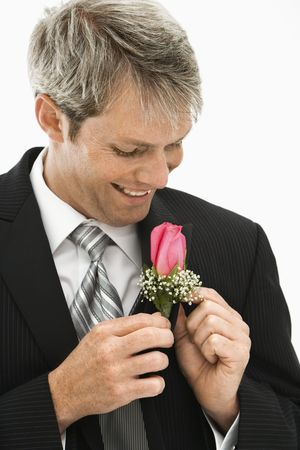 boutonniere: Caucasian groom adjusting boutonniere.