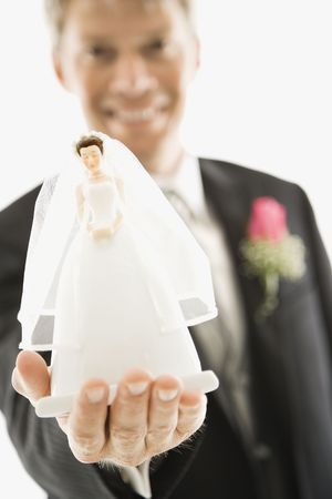 Caucasian groom holding out bride figurine in palm of his hand. photo