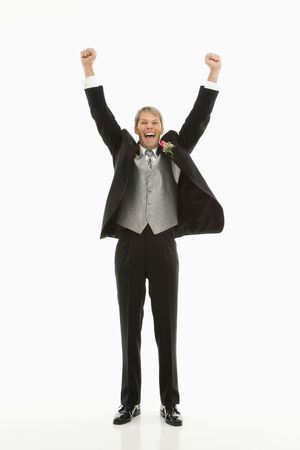 Caucasian groom with arms raised in air. photo