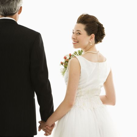 Asian bride looking over her shoulder while holding Caucasian groom's hand. Stock Photo - 2145690