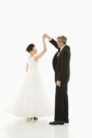 Portrait of Caucasian groom and Asian bride dancing. Stock Photo