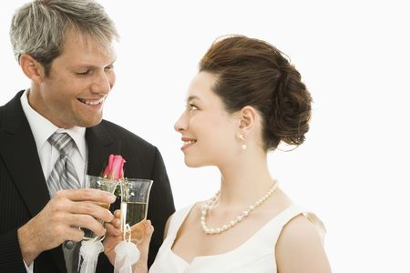 Caucasian groom and Asian bride toasting with champagne glasses. photo