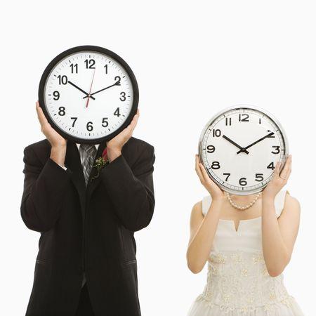 woman clock: El retrato del cauc�sico prepara y novia asi�tica con los relojes que cubren sus caras. Foto de archivo