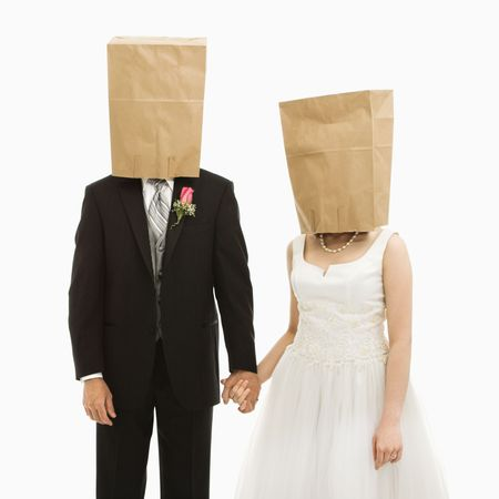 Caucasian groom and Asian bride with brown paper bags over their heads. photo