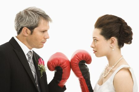 Caucasian groom and Asian bride wearing boxing gloves.