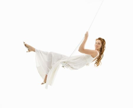 Caucasian bride swinging in swing set and looking at viewer.
