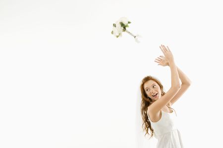 Portrait of Caucasian bride tossing bouquet behind her. Stock Photo