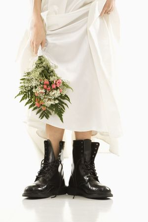 boot: Caucasian bride holding bouquet down by her black combat boots.