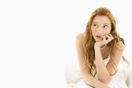 Portrait of sitting Caucasian bride biting her finger and looking off to the side.  Stock Photo - 2147396