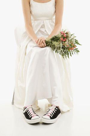 Caucasian bride holding bouquet exposing her tennis shoes.