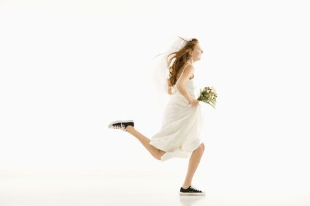 Caucasian bride running and holding bouquet. photo