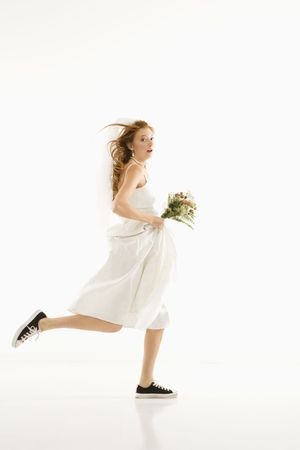 fear: Caucasian bride running and holding bouquet.