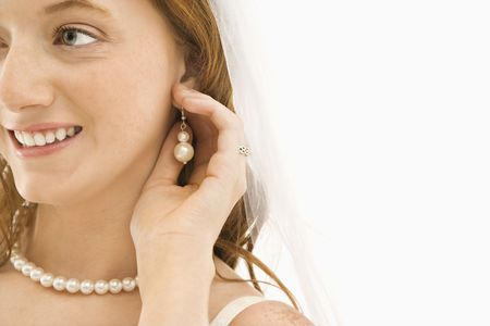 Caucasian bride adjusting her earring. photo