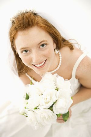 Portrait of a Caucasian bride holding bouquet looking up towards viewer. photo