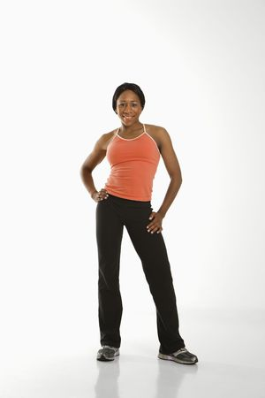 athletic wear: African American young adult woman in athletic wear smiling at viewer with hands on hips. Stock Photo