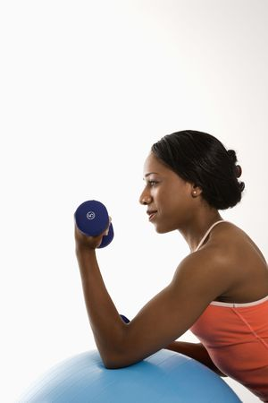Profile of African American young adult woman leaning on exercise ball holding dumbbell. photo