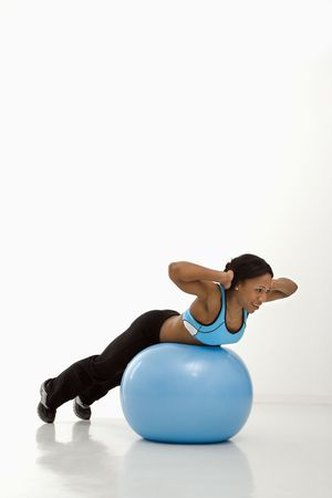 African American young adult woman working out with exercise ball. photo