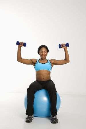 africanamerican: African American young adult woman sitting on exercise ball and raising dumbbells over head.