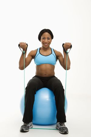 sport wear: African American young adult woman sitting on exercise ball using resistance tube.