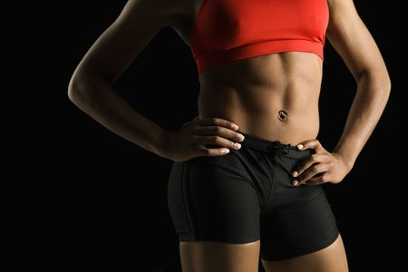 Torso of muscular African American woman wearing athletic apparel with hands on hips. Stock Photo