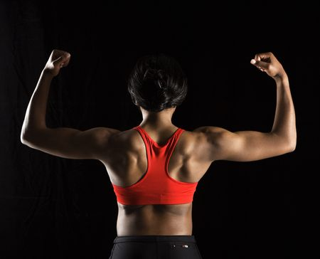 flexed: Back of muscular African American woman with biceps flexed. Stock Photo