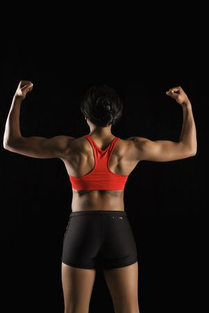 flexed: Back view of muscular African American woman with biceps flexed.