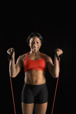 resistance: African American young adult woman exercising with resistance tube and smiling at viewer.