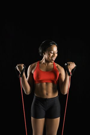 resistance: Smiling African American young adult woman exercising with resistance tube.