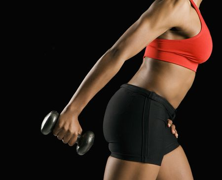 Side view if torso of African American young adult woman holding dumbbell outstretched. photo