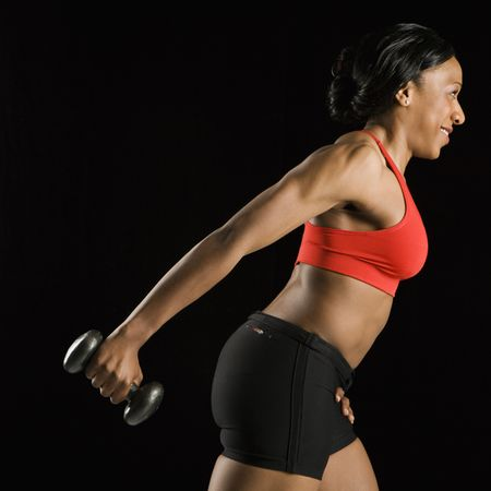 Profile of African American young adult woman holding dumbbell outstretched. Stock Photo - 2147474