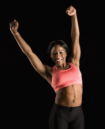 arms above head: Smiling African American young adult woman in sports bra stretching arms above head.